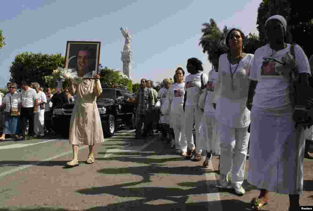 Integrantes de las Damas de Blanco caminan junto al cortejo fúnebre de Oswaldo Payá antes del funeral, celebrado este martes 24 de julio.
