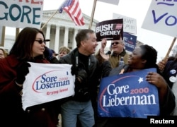 FILE - Supporters of Democrat U.S. Vice President Al Gore (R) and Republican Texas Governor George W. Bush face off against one another in front of the U. S. Supreme Court.