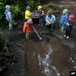 These children at Cedarsong Nature School on Vashon Island, near Seattle, Washington, are playing in a puddle. (AP Photo/Ted S. Warren, 2010)