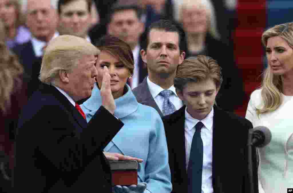El presidente de EE. UU. Donald Trump (izquierda) toma el juramento del presidente del Tribunal Supremo de EE. UU. John Roberts, junto a su esposa Melania, y los hijos Barron, Donald, Ivanka y Tiffany a su lado durante las ceremonias de inauguración en el Capitolio de Washington, el 20 de enero de 2017.