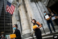 FILE - In this July 11, 2020, file photo, mourners carry out the remains of loved ones following the blessing of the ashes of Mexicans who died from COVID-19 at St. Patrick's Cathedral in New York.(AP Photo/Eduardo Munoz Alvarez, File)