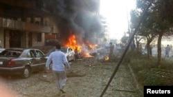 Seorang pria berjalan di dekat mobil yang terbakar pasca ledakan di dekat Kedutaan Iran di Beirut (19/11).