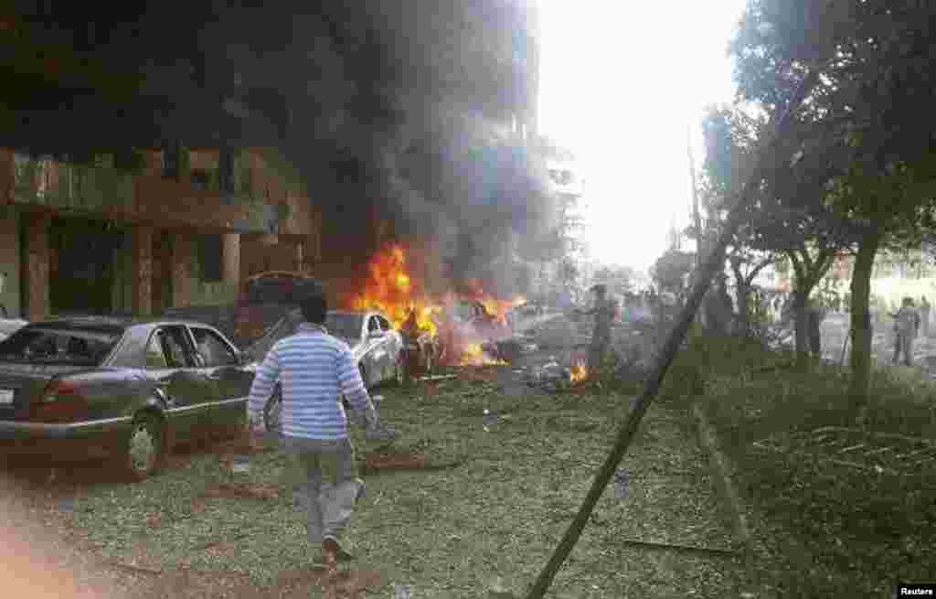 A man walks near burning cars at the site of explosions near the Iranian embassy in Beirut, Nov 19, 2013.
