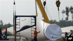 Workers prepare to lift a giant blade to be used as part of wind turbines at the Vestas Wind Technology Co. Ltd. factory in Tianjin, China, (File)