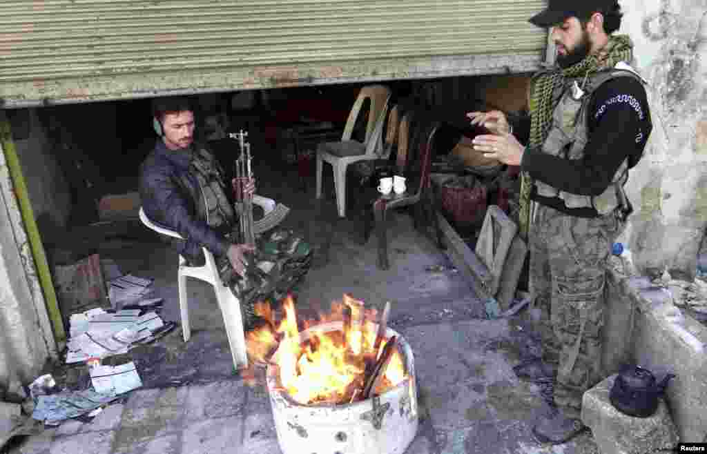 Free Syrian Army fighters warm themselves by a fire in Aleppo's al-Amereya district, December 11, 2012.