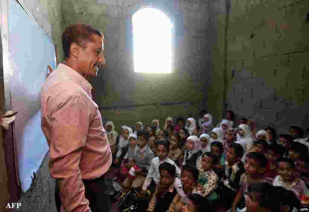 جنگ سے تباہ حال یمن کے شہر تعز میں ایک استاد بچوں کوسبق پڑھاتے ہوئے، یونیسیف کے مطابق یمن میں تین سال سے جاری جنگ کی وجہ سے 20 لاکھ بچے تعلیم سے محروم ہیں
