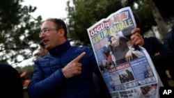 """FILE - A man shows the front page of the daily Ozgur with a headline that reads """" bloody intervention"""" as people gather outside the headquarters of Zaman newspaper in Istanbul, March 6, 2016."""