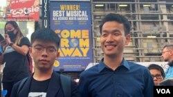 梁繼平(右)9月15日與黃之鋒一起到紐約時報廣場高唱榮光歸香港的歌曲。(美國之音中文部)