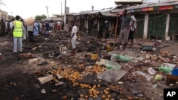 FILE - People gather at the scene of a car bomb explosion at the central market in Maiduguri, Nigeria, July 2, 2014.