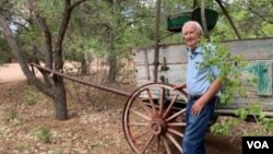 Forrest Fenn stands in front of an original 19th century cart he had placed on the old Santa Fe trail running through his property. (VOA/Penelope Poulou)