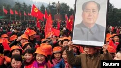 A man holds up a portrait of the late Chairman Mao Zedong as he and others gather in front of a giant statue of Mao on a square to celebrate the 120th birth anniversary of the former leader, in Shaoshan, Mao's hometown, Dec. 26, 2013.