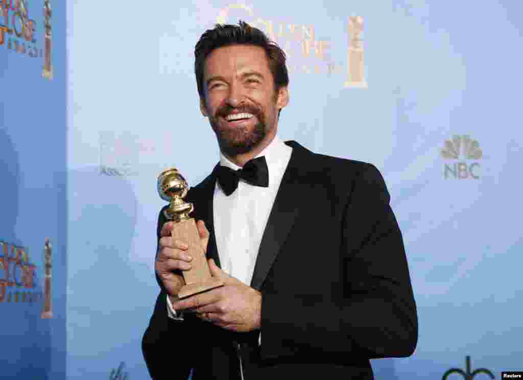 "Actor Hugh Jackman holds up the award he won for Best Performance by an Actor in a Motion Picture Musical or Comedy for his performance in ""Les Miserables,"" at the 70th annual Golden Globe Awards in Beverly Hills, California January 13, 2013."