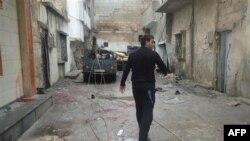 Một người đàn ông đi bộ qua một con đường đầy vỏ đạn trong thành phố Homs, Syria