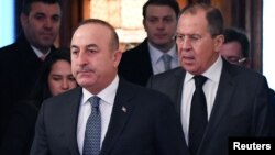 Russian Foreign Minister Sergei Lavrov, right, and his Turkish counterpart, Mevlut Cavusoglu, enter a hall as they meet in Moscow, Russia, Dec. 20, 2016.