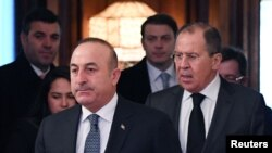 Russian Foreign Minister Sergey Lavrov, right, and his Turkish counterpart, Mevlut Cavusoglu, enter a hall as they meet in Moscow, Russia, Dec. 20, 2016.