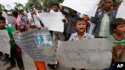 "FILE - A boy holds a banner reading ""Please stop grabbing our land"" at a rally by land eviction victims in front of the National Assembly in Phnom Penh, Cambodia, Sept. 1, 2014."