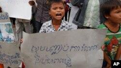 Một cậu bé cầm biểu ngữ 'Hãy ngưng lấy đất của chúng tôi' tại một cuộc biểu tình của các nạn nhân bị chiếm đoạt đất đai phi pháp, ở Phnom Penh, Campuchia, ngày 1/9/2014. (Ảnh tư liệu)
