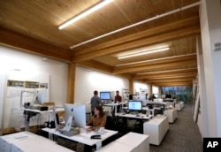 FILE - An upper floor of Lever Architecture headquarters, a four-story all-wood building built using cross-laminated timber stands in Portland, Ore., Nov. 15, 2016.