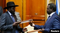 South Sudan's President Salva Kiir (L) and the country's rebel leader, Riek Machar, exchange signed peace agreement documents in Addis Ababa May 9, 2014.