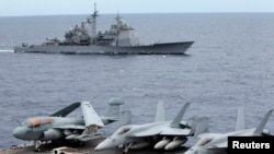 FILE - U.S. fighter jets on standby at the upper deck of a USS George Washington aircraft carrier while the USS Cowpens passes by, in the South China Sea, 170 nautical miles from Manila, September 2010.