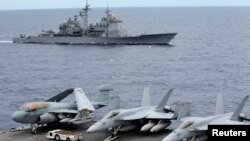 Chiến đấu cơ của Mỹ đậu trên tàu sân bay USS George Washington. Phía sau là tàu tuần dương có tên lửa dẫn đường USS Cowpens trong khu vực Biển Đông, 170 hải lý từ Manila (Ảnh tư liệu).