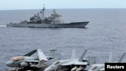 FILE - U.S fighter jets on standby at the upper deck of a USS George Washington aircraft carrier while the USS Cowpens passes by, in the South China Sea, 170 nautical miles from Manila.