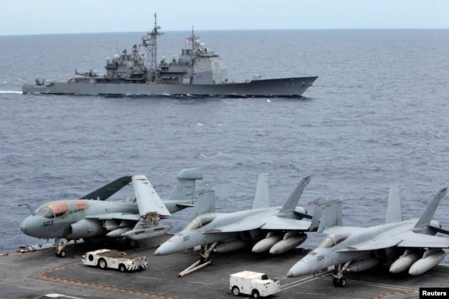 FILE - U.S fighter jets on standby on USS George Washington aircraft carrier while the USS Cowpens passes by, in the South China Sea, 170 nautical miles from Manila, Sept. 2010.