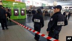 Polisi berjaga dekat lokasi penusukan seorang tentara Perancis di distrik komersial La Defense, di luar kota Paris (25/5). (AP/Remy de la Mauviniere)