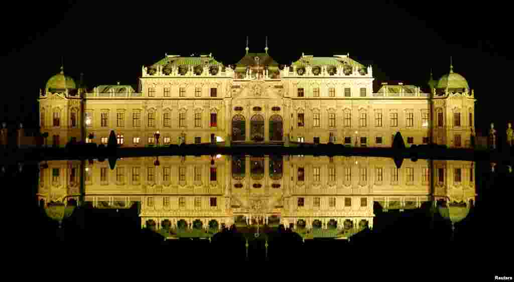 Belvedere palace is reflected in a pond are seen before the lights were switched off for Earth Hour in Vienna, Austria, March 25, 2017.