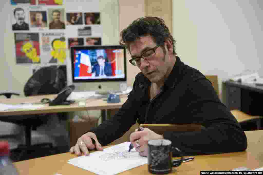 Riss Tignous sketches a political cartoon in the boardroom of Parisian satirical paper Charlie Hebdo in 2012. He was among twelve killed when masked gunmen opened fire in the paper's office on January 8, 2015.