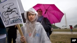 In a steady rain storm near the Washington Monument, Anastasia Bardin, 10, of New York City, left, with her mother Lyn Bardin, rallies with the Earth Action Team as part of Earth Day activities on the National Mall in Washington Sunday, April 22, 2012.