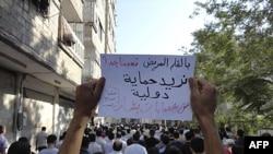Người trong đoàn biểu tình ở Syria chống Tổng thống Bashar al-Assad cầm tấm bảng với dòng chữ 'Cần sự can thiệp của quốc tế để bảo vệ chúng tôi khỏi bè lũ của Bashar'