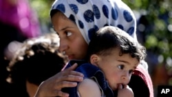 Syrian refugee girl carries her sister in Ketermaya village southeast of Beirut, Lebanon.