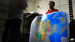 FILE - A worker holds a new officially approved map of China that includes the islands and maritime area that Beijing claims in the South China Sea, at a printing factory in Changsha in south China's Hunan province.