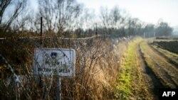 """Papan bertuliskan """"Perhatian! Perbatasan Negara"""" terlihat dipasang pada pagar kawat berduri di perbatasan Slovenia-Kroasia, dekat desa Rigonce, Slovenia, 16 Februari 2017. (Foto: dok)."""