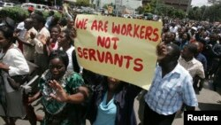 FILE - Zimbabwe's civil servants carry placards as they march during a protest in the streets of the capital Harare, Feb. 19, 2010.