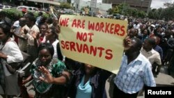 FILE - Zimbabwe's civil servants carry placards as they march during a protest in the streets of the capital Harare, Feb. 19, 2010. Government has failed to pay civil servants their 2016 bonuses due to a lack of funds. An offer to substitute the bonus with land was rejected by unions.