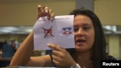 Una miembro de una mesa de votación muestra una papeleta marcada por el partido FMLN, que según el Tribunal Supremo Electoral, ganó la elección por un ajustado margen.