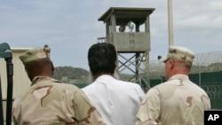 Un prisonnier escorté par des gardes à Guantanamo