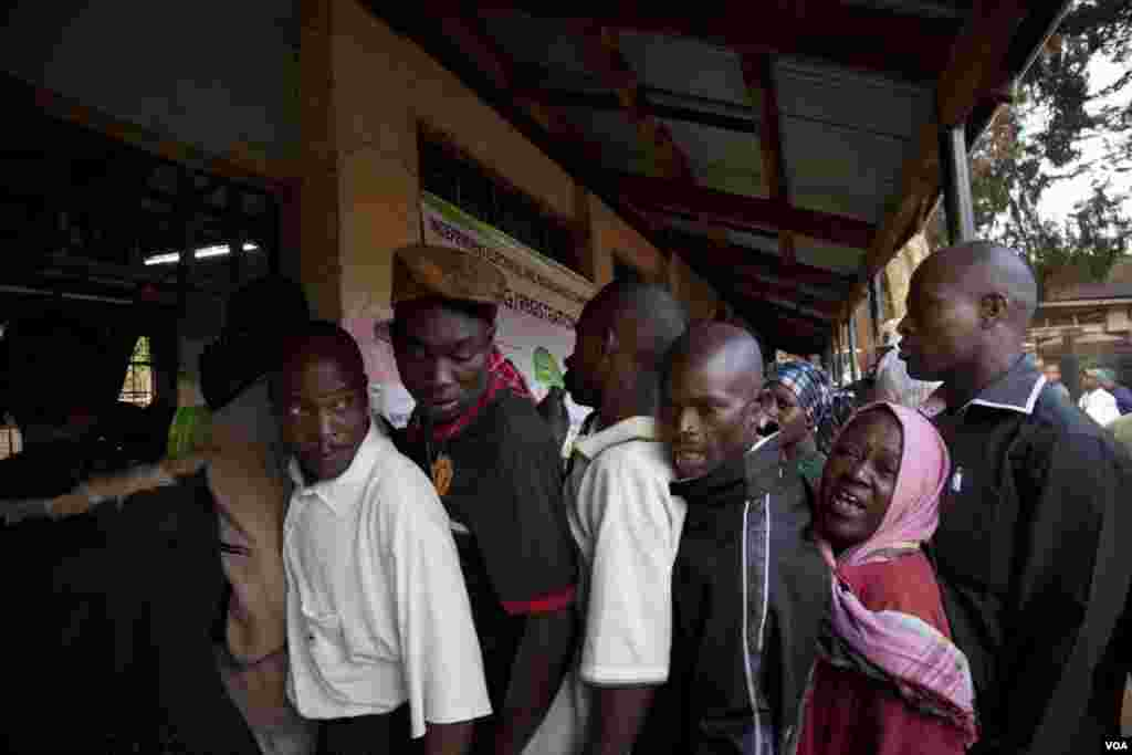 After waiting in line for more than six hours, voters complained about delays in opening the polls to an IEBC official at the Kibera Primary School, March 4, 2013. (R. Gogineni/VOA)