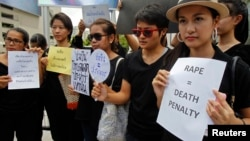 FILE - Thai social media users hold banners during a rally calling for the death penalty for rapists, outside a shopping mall in Bangkok, July 12, 2014.