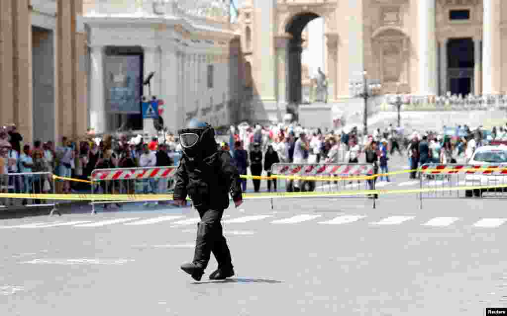A police officer from the bomb disposal unit checks the area after an alarm near the Vatican, in Rome, Italy.