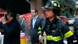 Губернатор штата Нью-Йорк Эндрю Куомо (в центре) рядом со зданием, на крыше которого разбился вертолет.