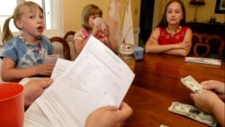 Three sisters in Ohio wait as their parents count out their allowances and look over the list of the children's chores