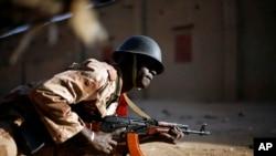 Un soldat malien s'abrite derrière un véhicule à Gao lors d'échanges de tirs avec des djihadistes (10 fév. 2013)