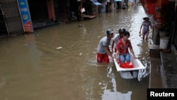Men use a bathtub to ferry a woman on a flooded street caused by typhoon Kai Tak - RTR36XQY