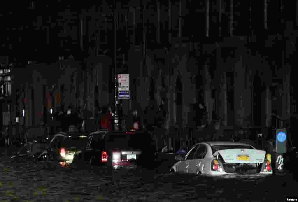 Flood waters brought on by Hurricane Sandy over run cars in New York's lower east side, October 29, 2012. Hurricane Sandy began battering the U.S. East Coast on Monday with fierce winds and driving rain, as the monster storm shut down transportation, shut