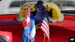 在古巴哈瓦那的街上,一部計程車掛上美國和古巴的國旗,準備迎接奧巴馬的到訪。