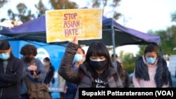 An Asian-American woman rases a sign during a peace vigil to mourn the victims of anti-Asian hate crimes at Almansor Park, Alhambra, California, U.S., March 21, 2021.