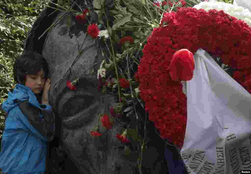 Một cậu bé bên tượng đài trong trường Đại học Bách khoa Athens, hai ngày trước ngày kỷ niệm sự kiện sinh viên nổi dậy năm 1973 chống lại chính quyền quân sự khi đó đang cầm quyền tại Athens, Hy Lạp.